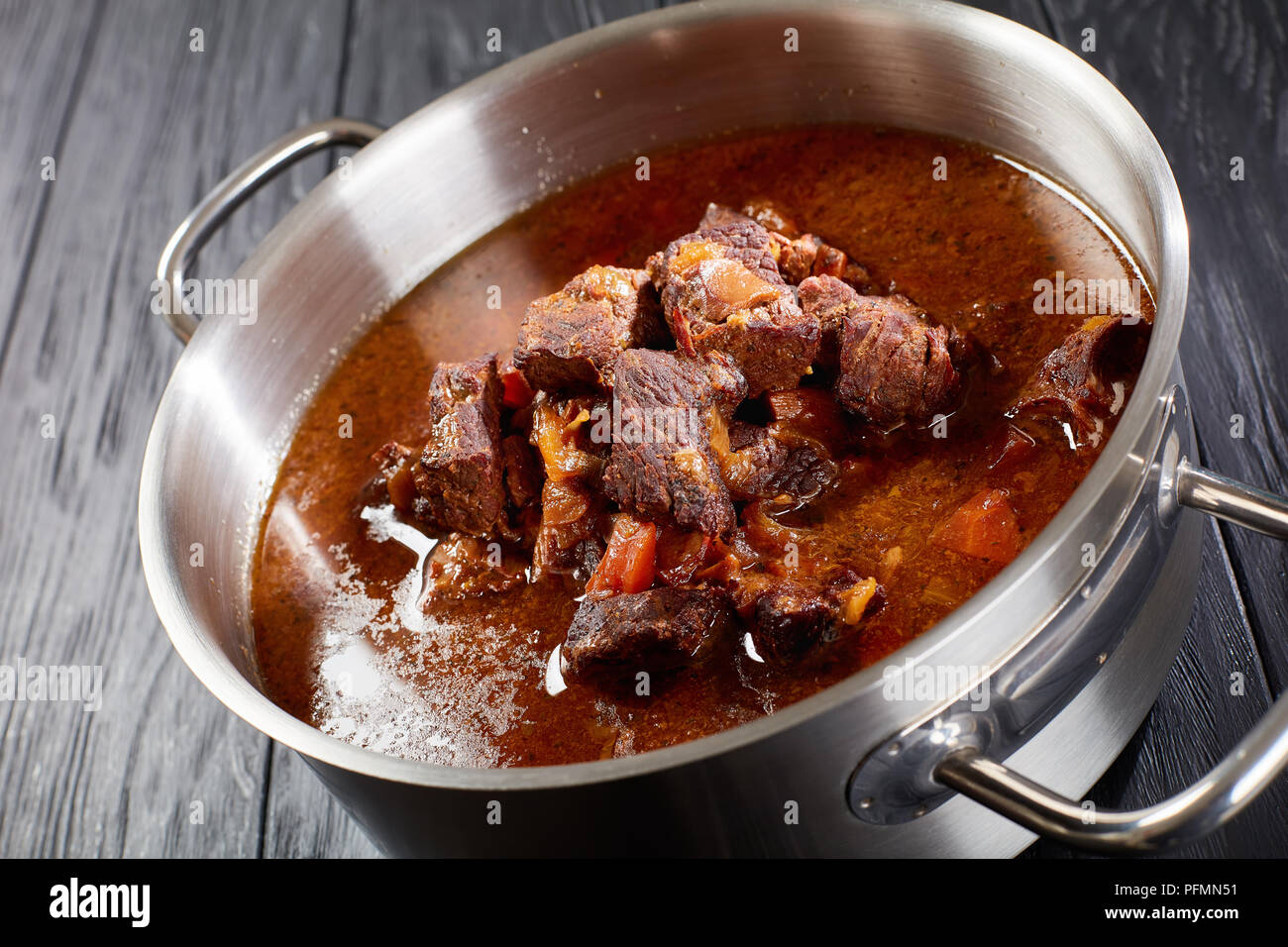 close-up of delicious homemade hot Czech beef goulash in a stainless pan on black wooden table, view from above Stock Photo