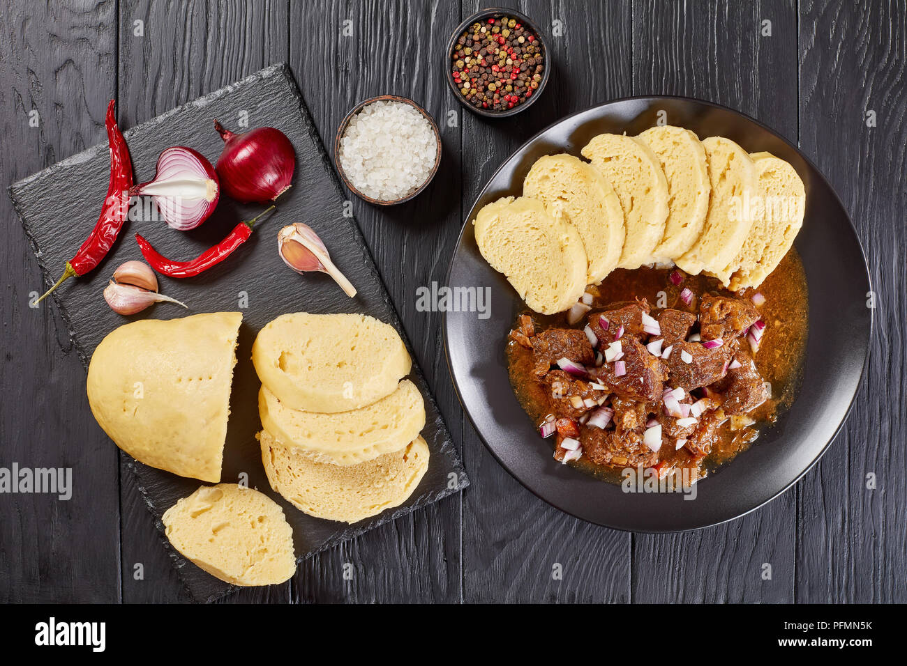 delicious homemade hot traditional Czech beef goulash served with steamed czech dumplings or knodel on black plate on wooden table with ingredients at - Stock Image