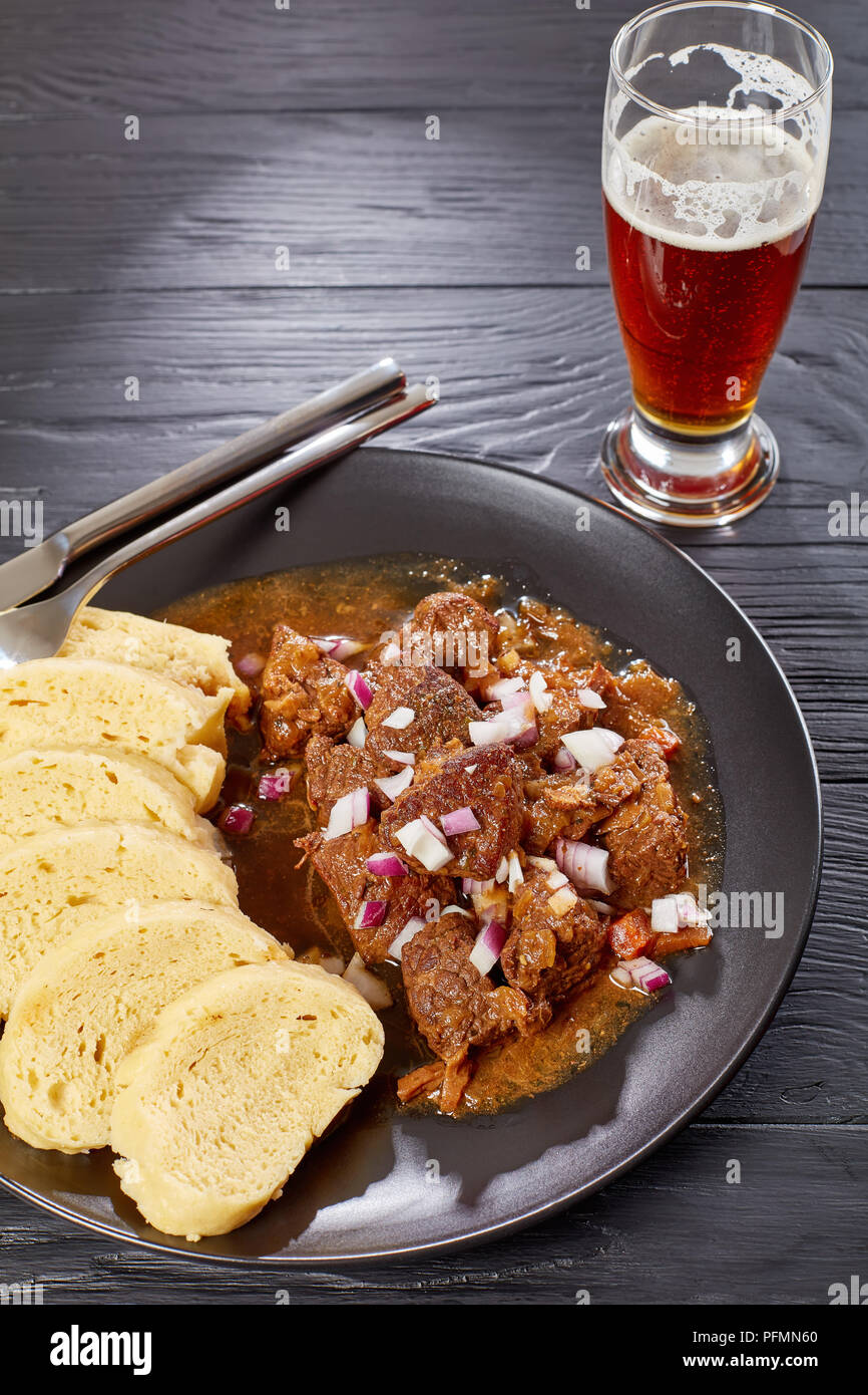 delicious homemade hot traditional Czech beef goulash served with steamed czech dumplings or knedliky on black plate on wooden table with glass of bee - Stock Image
