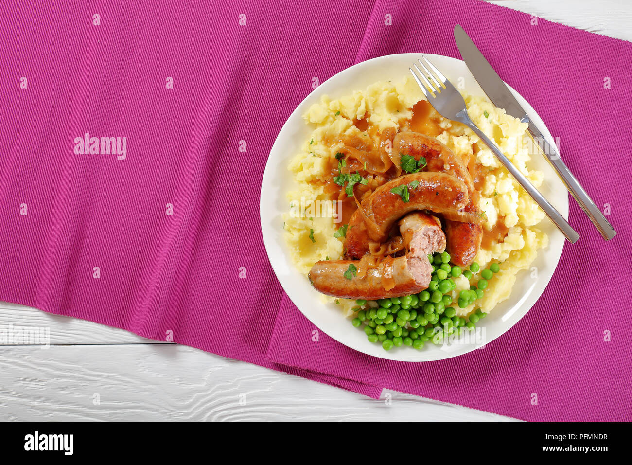 delicious Bangers and Mash -  juicy fried sausages drowning in loads of gravy, with creamy mashed potatoes and the obligatory side of peas, classic re Stock Photo