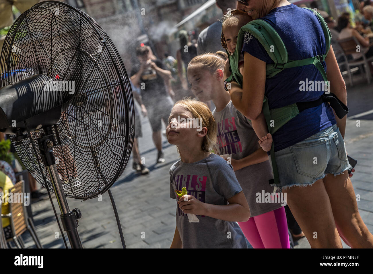 BUDAPEST,HUNGARY-AUGUST 09,2018:People alleviate the summer heat wave in front of the water spraying fan at the street of downtown. - Stock Image