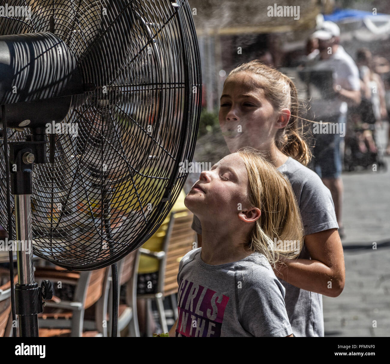 BUDAPEST,HUNGARY-AUGUST 09,2018:People alleviate the summer heat wave in front of the water spraying fan at the street of downtown. Stock Photo