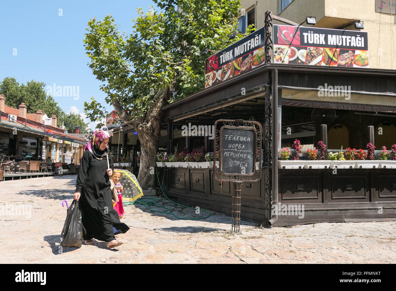 Skopje Old Bazaar - Muslim woman and small child walking past a Turkish food shop or restaurant, Skopje, Macedonia - Stock Image
