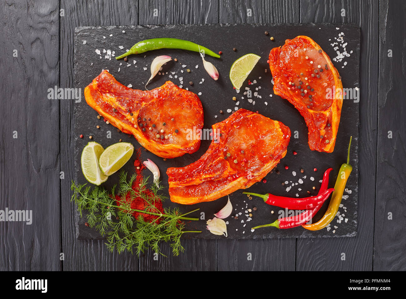raw pork chops marinated with spices and red sriracha sauce on black slate tray with chili pepper, salt, lime slices and spices, view from above, flat Stock Photo