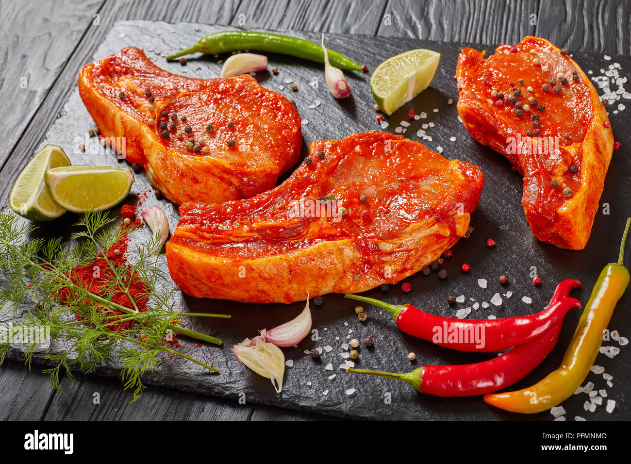 raw pork chops prepared to cook, marinated with spices and red sriracha sauce on black slate tray with chili pepper, salt, lime slices and spices, vie Stock Photo