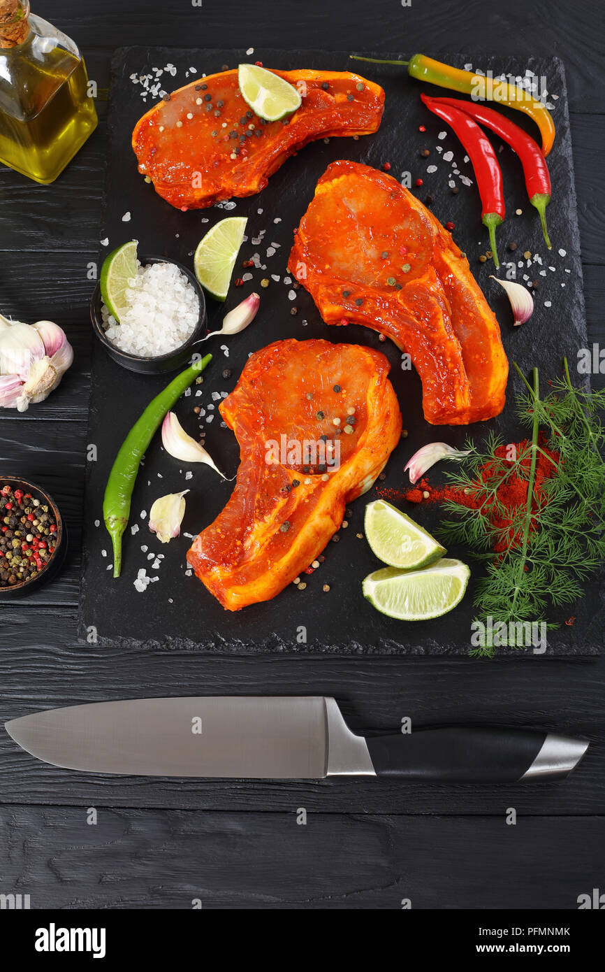 raw pork cutlets prepared to roast, marinated with spices and red sriracha sauce on black slate tray with chili pepper, salt, lime slices and spices o - Stock Image