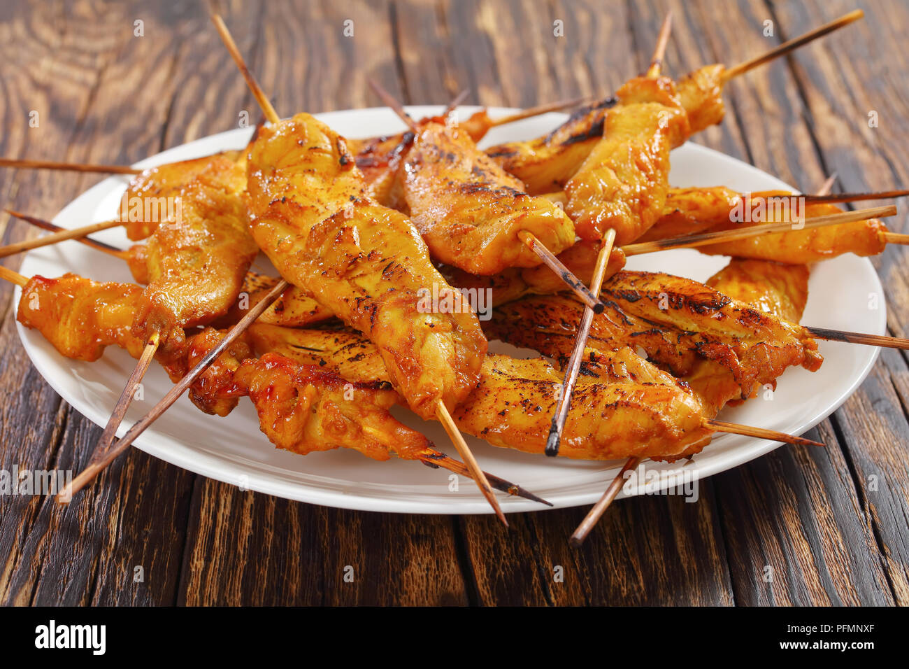 close-up of grilled Chicken satay on skewers on a white plate on rustic wooden table, classic recipe, street food, view from above - Stock Image
