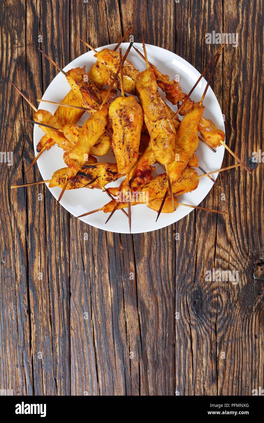 Chicken satay on skewers on a white plate on rustic wooden table, authentic recipe, street food, vertical view from above - Stock Image