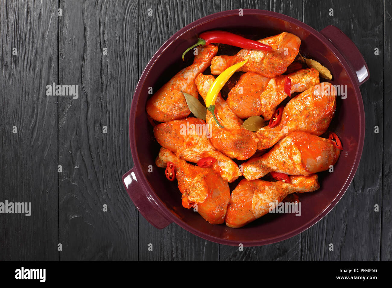 raw marinated chicken drumsticks rubbed with finely ground spice, chili pepper pieces, bay leaves  prepared to roast in a dish, view from above Stock Photo