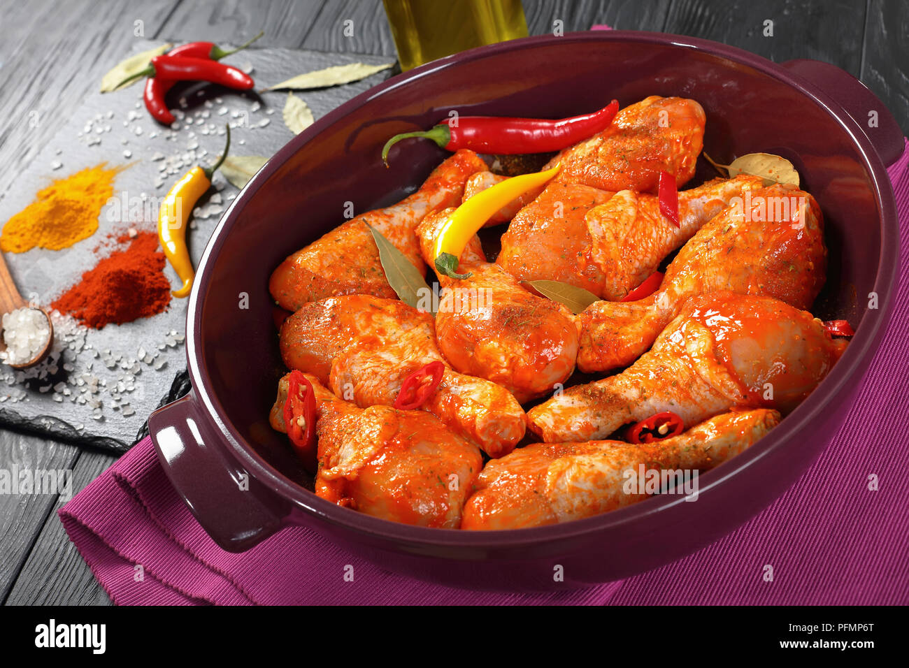 raw marinated chicken drumsticks sprinkled with spice, chili pepper pieces, bay leaves  prepared to cook in a dish, ingredients on a stone board on a  Stock Photo