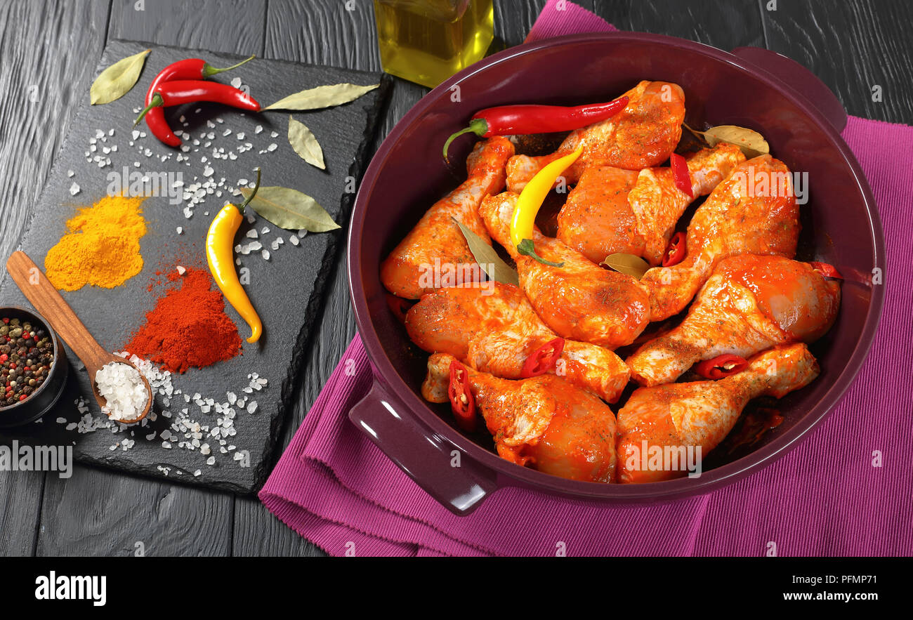 raw marinated chicken drumsticks sprinkled with spice, chili pepper pieces, bay leaves  prepared to cook in a dish, ingredients on a slate board on a  Stock Photo