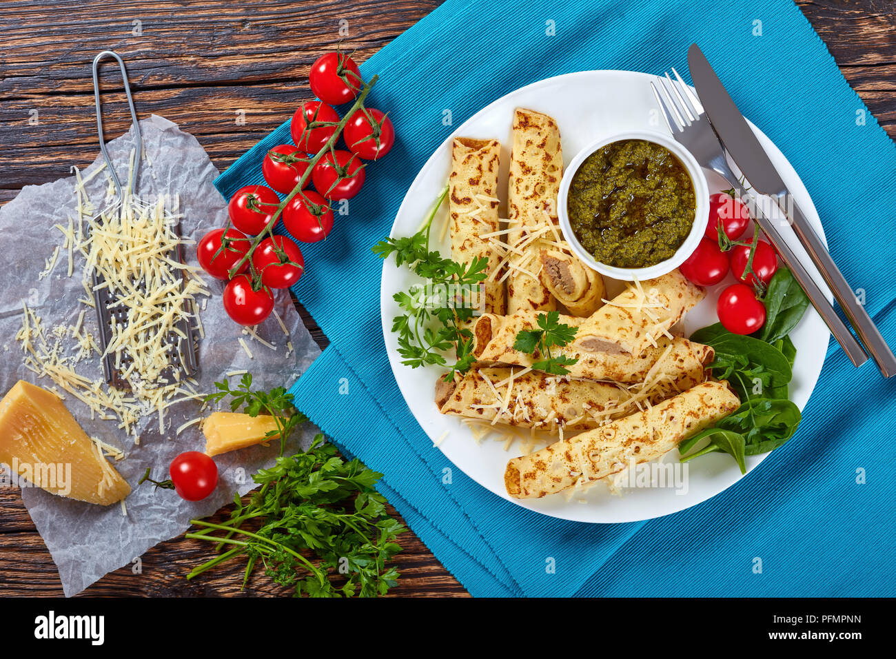 delicious fried crepes stuffed with chicken meat sprinkled with grated parmesan cheese, served on a white plate with spinach, cherry tomatoes and home - Stock Image