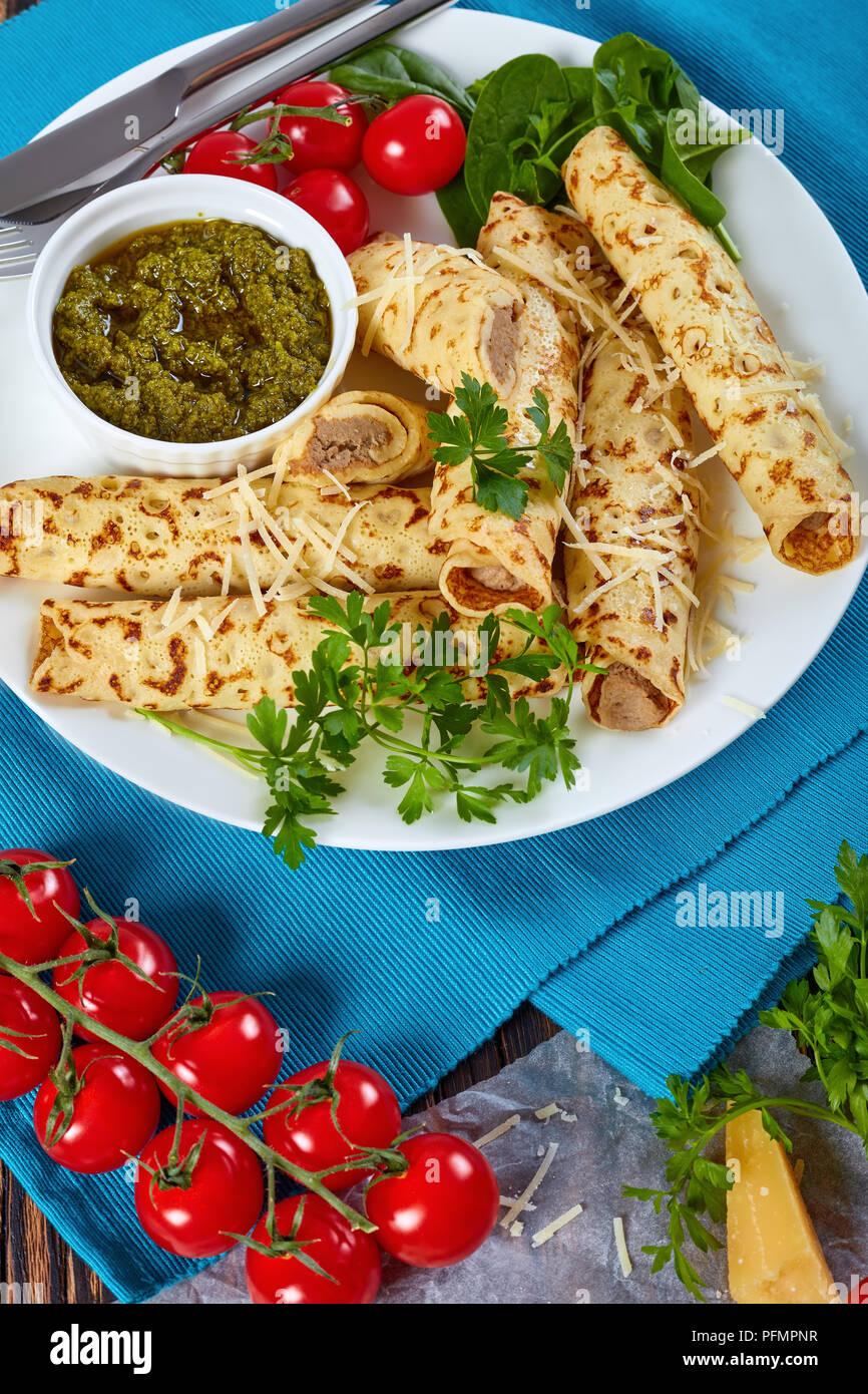 crepes stuffed with chicken meat sprinkled with grated parmesan cheese, served on a white plate with spinach, cherry tomatoes and homemade sauce pesto - Stock Image