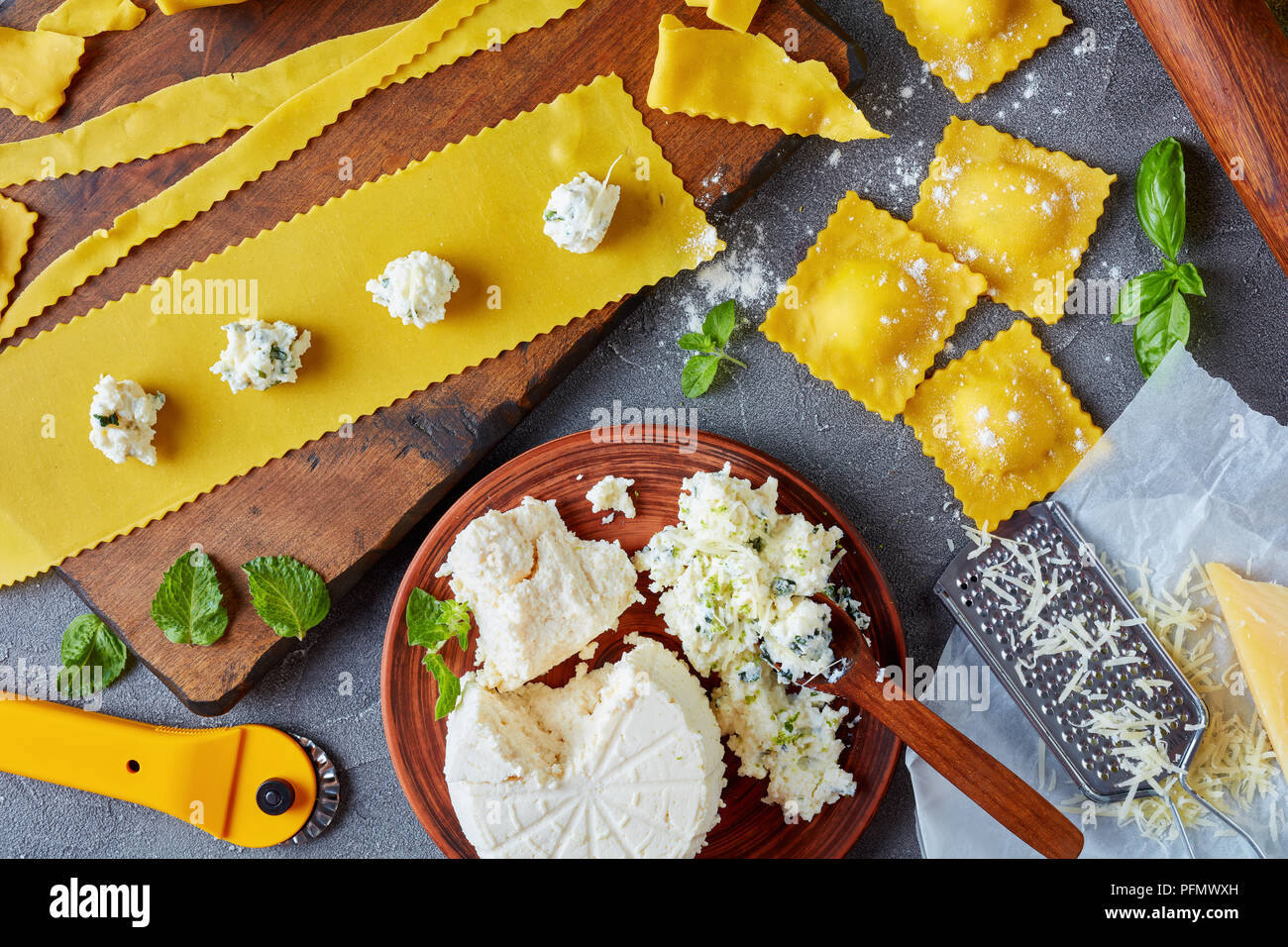 cooking up delicious ravioli with ricotta cheese filling mixed with finely chopped mint and basil leaves on a concrete kitchen table with ingredients, - Stock Image