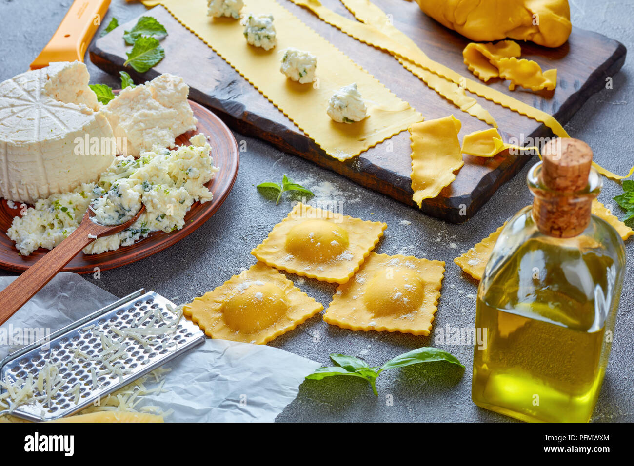 making up delicious ravioli with ricotta cheese filling mixed with finely chopped mint and basil leaves on a concrete kitchen table with ingredients,  - Stock Image