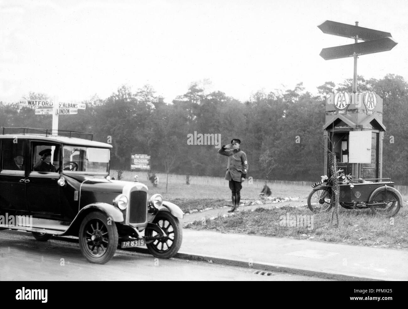 AA patrolman saluting motorist at Garston near Watford, 1920s maybe - Stock Image