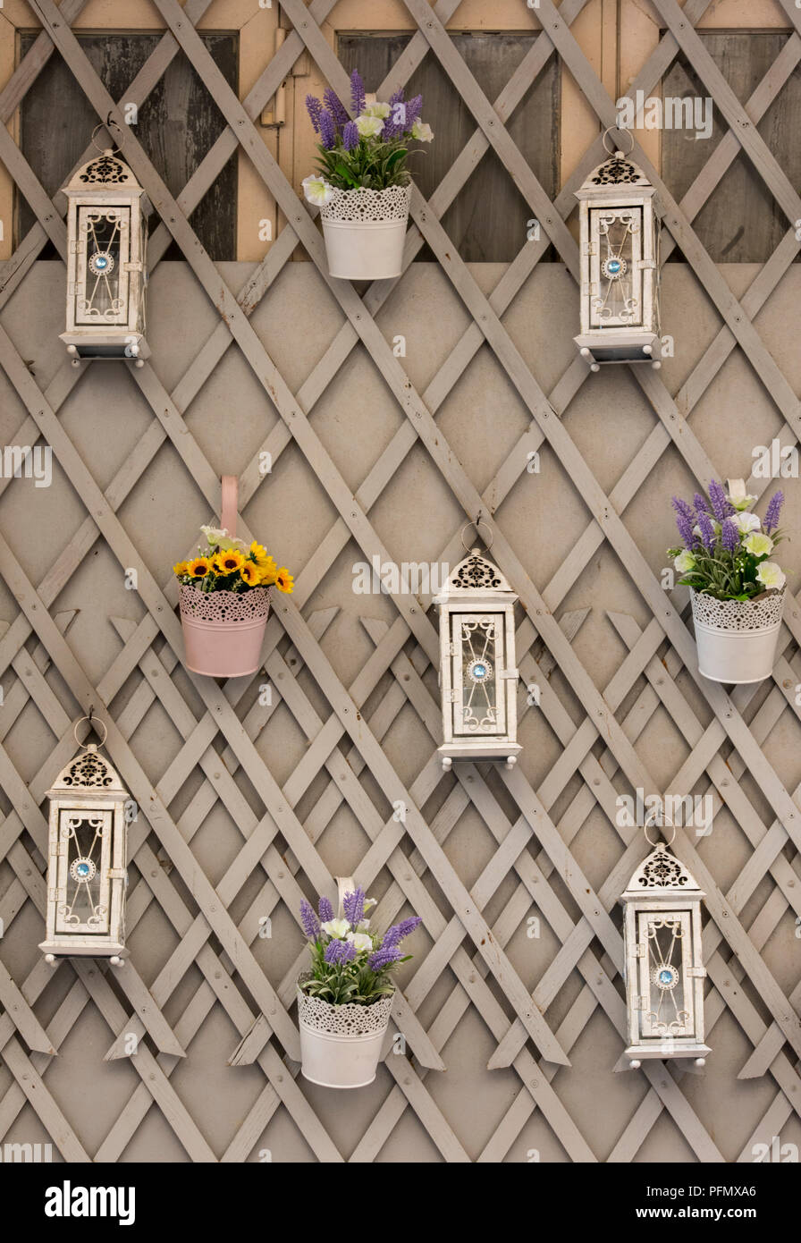 decorative flowers and lanterns hanging on some garden trellis for decorations . - Stock Image