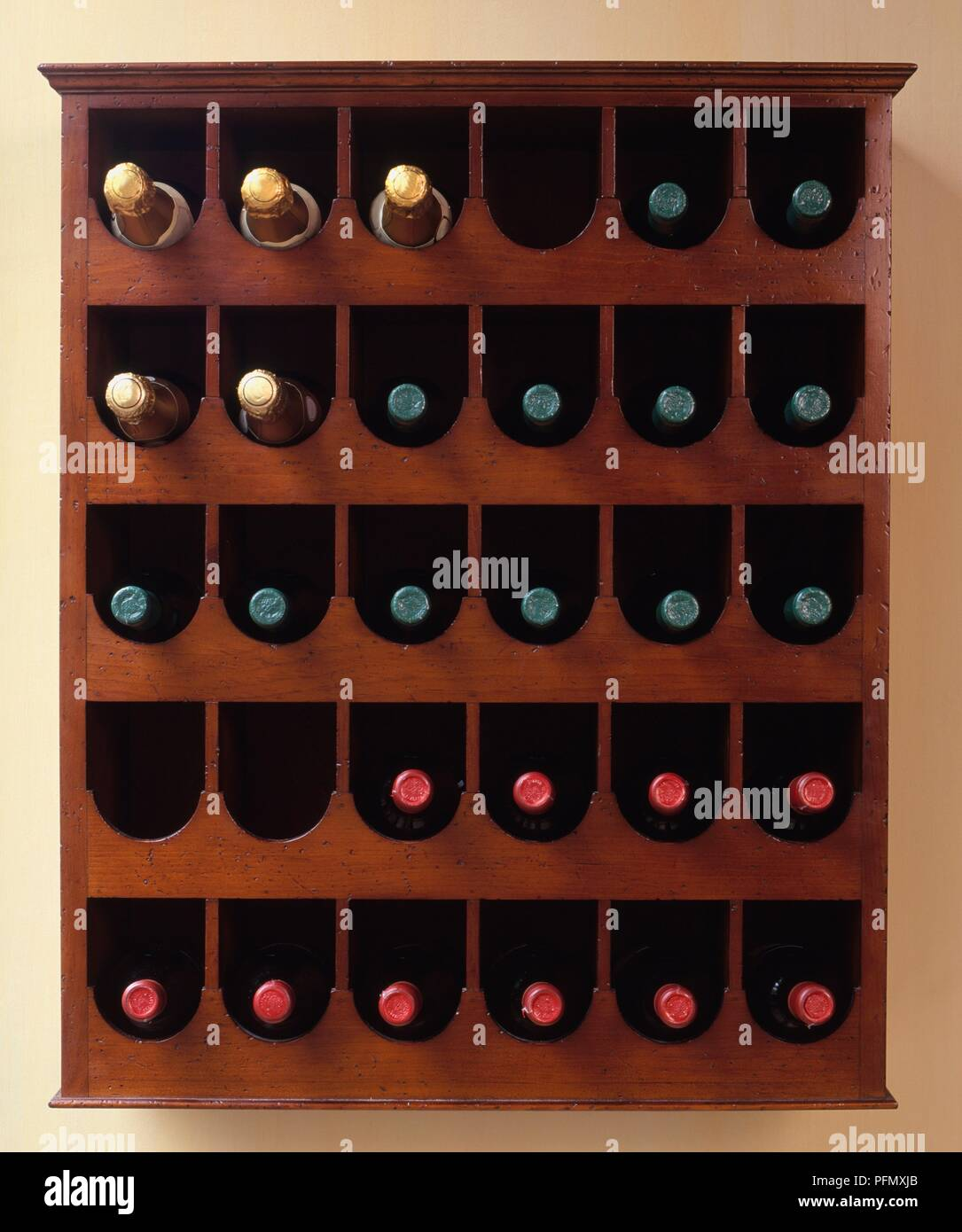 Bottles of Champagne and wine in polished wood rack - Stock Image