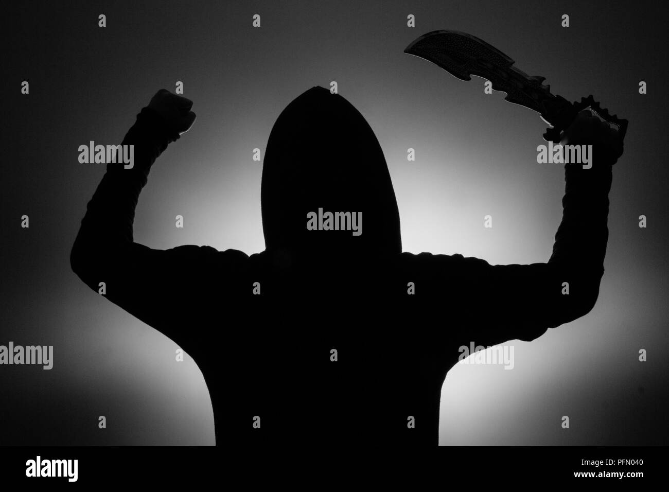black and white photo: silhouette of a man in a hood holding a fantasy sword in a hang raised in the air - Stock Image