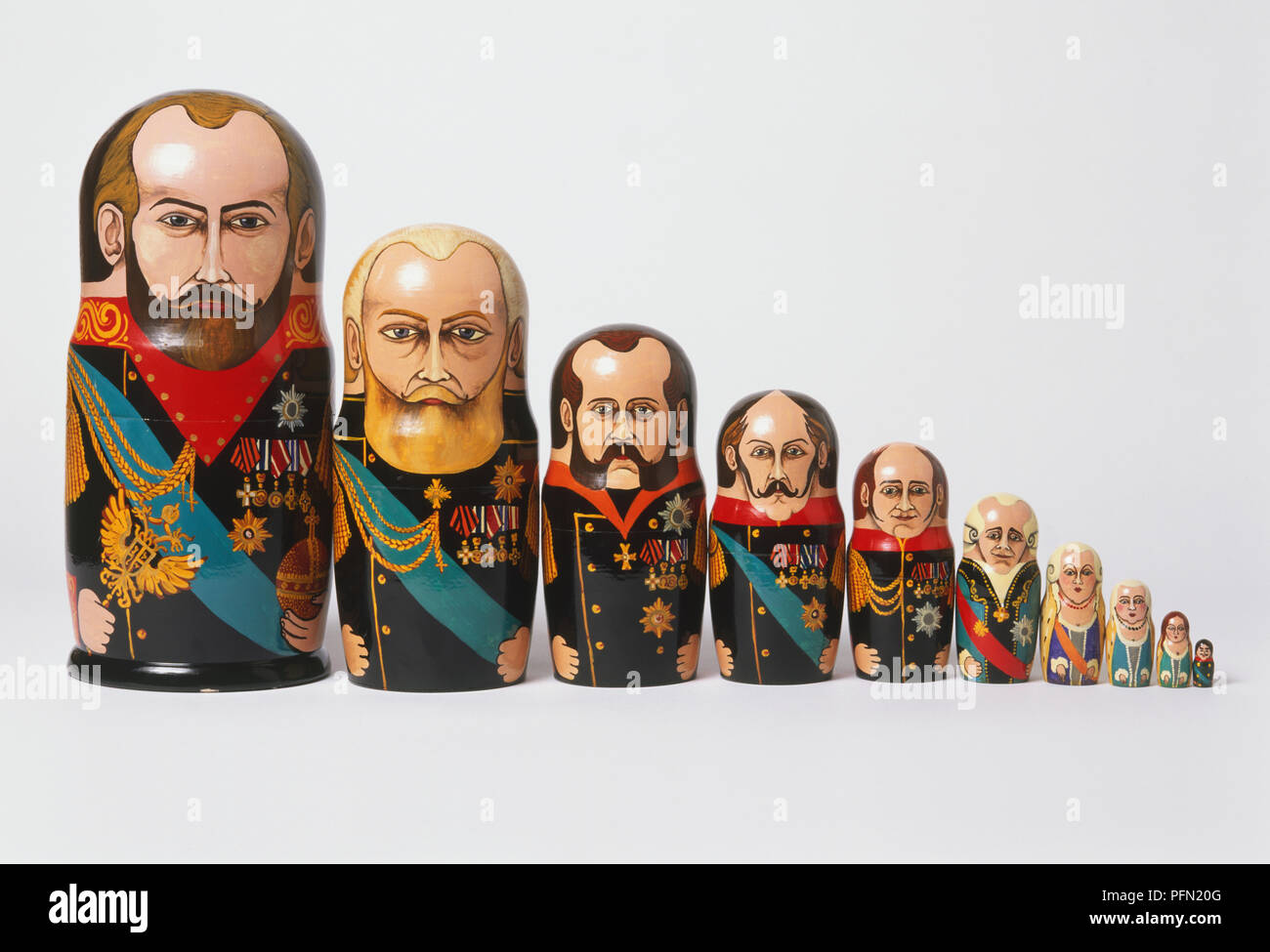 Row of Matryoshka-style dolls of gradually decreasing size, with iconography of military and political leaders. - Stock Image