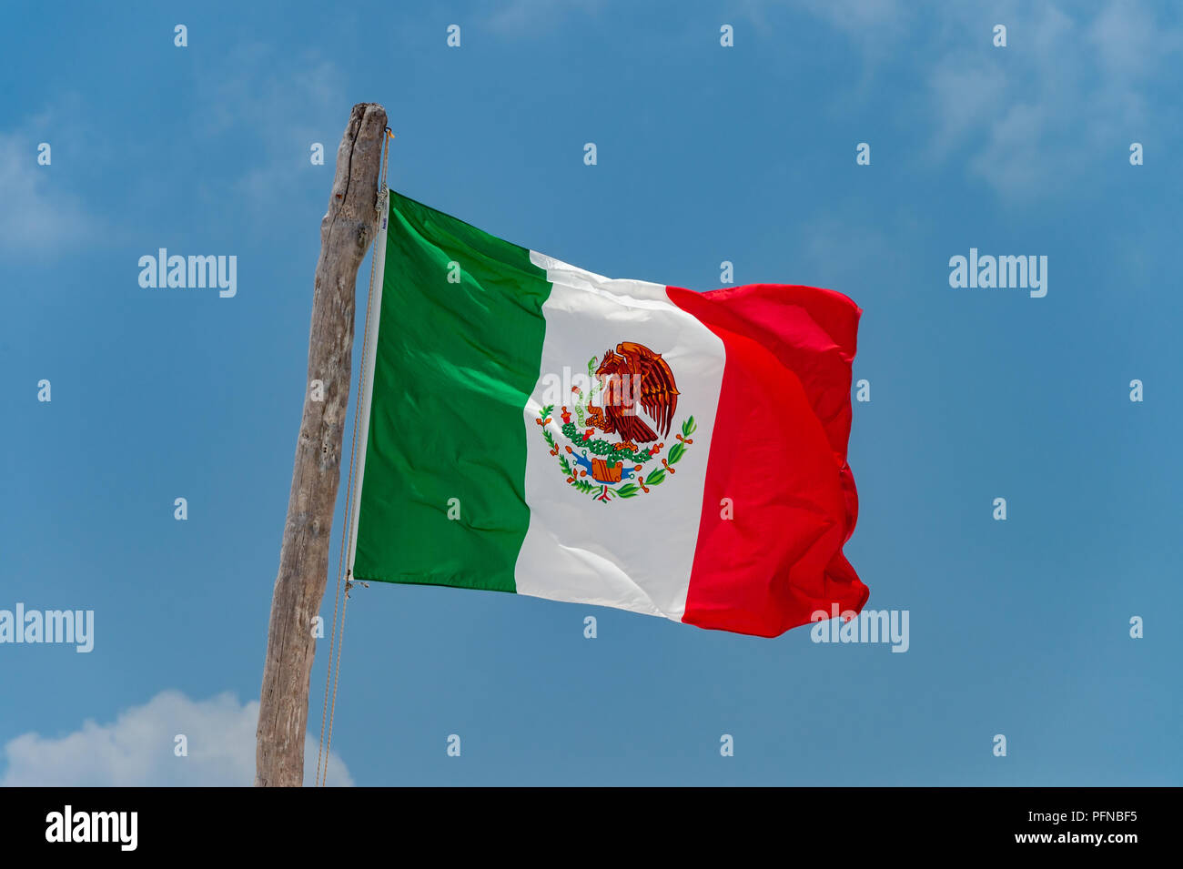 Mexican flag over blue sky in Tulum, Mexico. - Stock Image