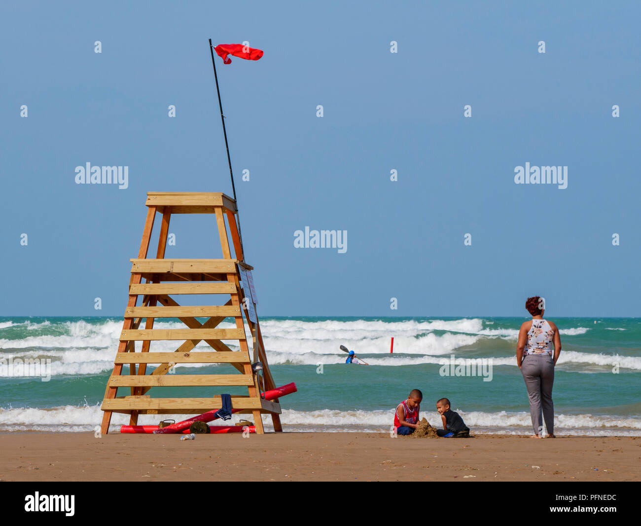 Chicago, Illinois, USA. 21st August 2018. Two children play in the sand while their mother stands by and a kayaker braves the waves at Montrose Beach. A red flag flies from a lifeguard stand indicating unsafe swiiming conditions caused by high surf and rip currents. Stiff northeast winds whipped up surf on Lake Michigan, bringing out kayakers, kite surfers and wave watchers. Credit: Todd Bannor/Alamy Live News Stock Photo