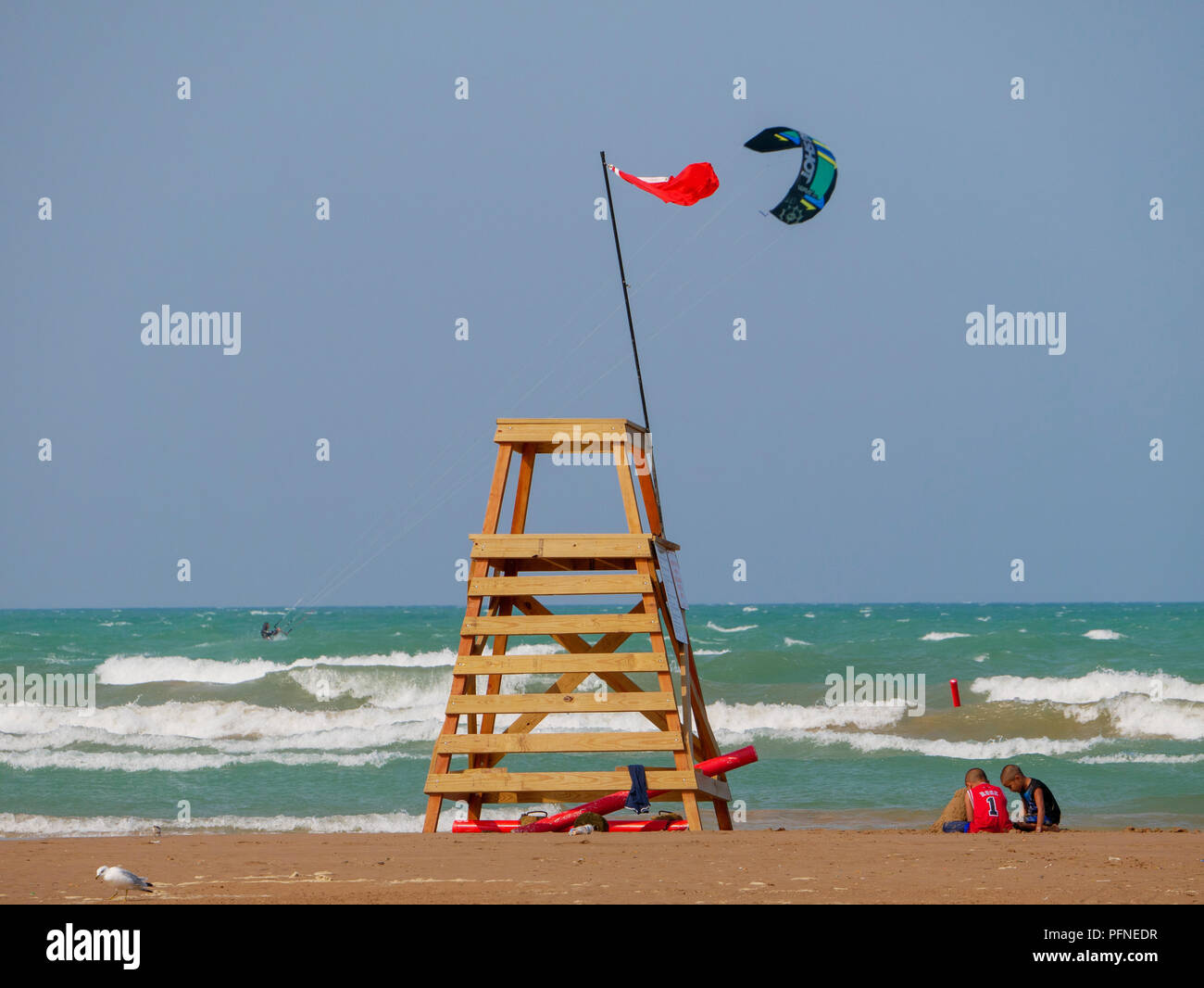 Chicago, Illinois, USA. 21st August 2018. A red flag indicating unsafe swimming conditions flies from a lifeguard stand at Montrose Beach as two children play in the sand and a kite surfer speeds by. Stiff northeast winds whipped up surf on Lake Michigan, bringing out kayakers, kite surfers and wave watchers. Credit: Todd Bannor/Alamy Live News Stock Photo