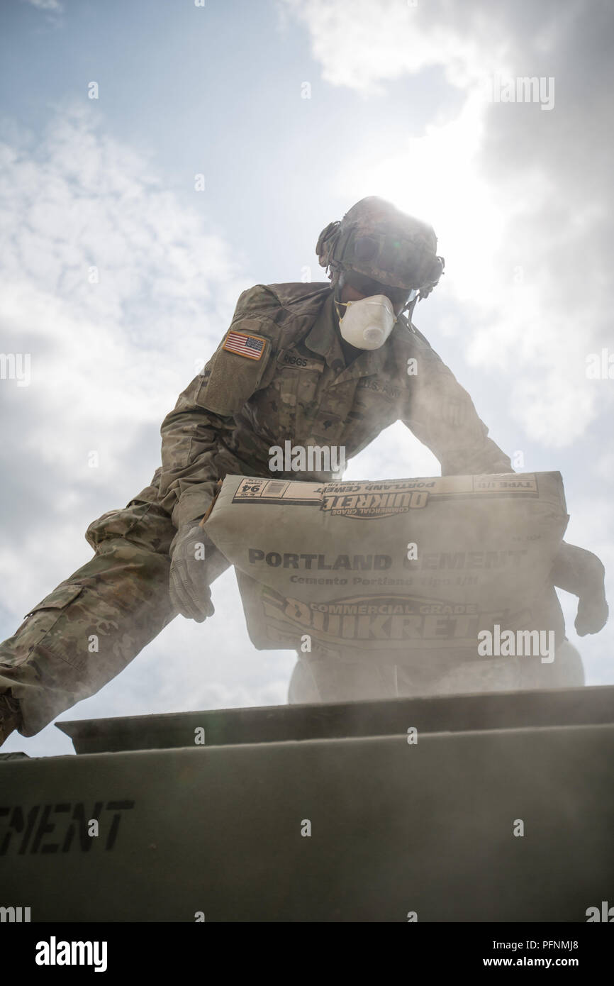 Fort Mccoy, Wisconsin, USA. 21st Aug, 2018. U.S. Army Reserve Spc. Marcelles Riggs, 943rd Engineer Detachment, 416th Engineer Command, loads a bag of concrete into an M5-Concrete Mobile Mixer during Combat Support Training Exercise (CSTX) 86-18-02 at Fort McCoy, Wis., August 16, 2018. This is the second CSTX of the summer for the 86th Training Division. The CSTX exercise is a large-scale training event where units experience tactical training scenarios specifically designed to replicate real-world missions. (U.S. Army Reserve Photo by Spc. John Russell) U.S. Department of Defense - Stock Image