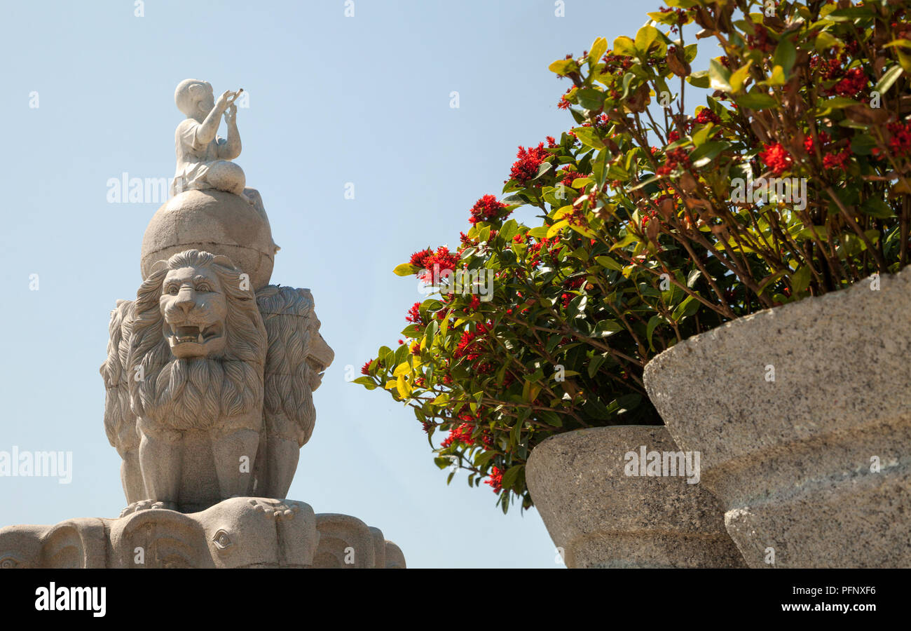 Three lions holding a globe sculpture near the Vinpearl amusement park. Decorative statue of animals at a garden with bright flowers in a flowerbed - Stock Image