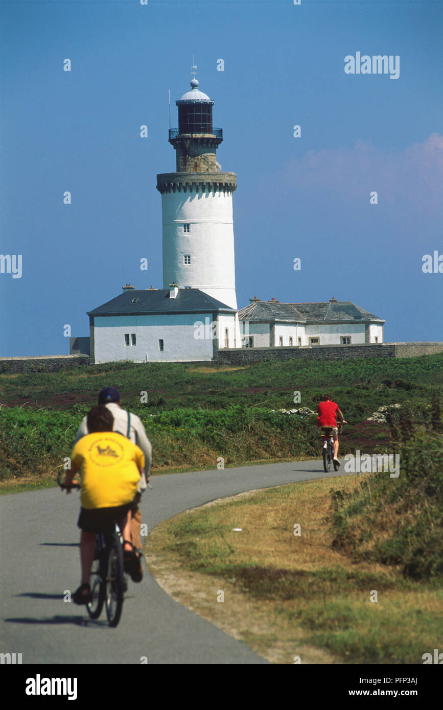 France, Brittany, Northern Finistere, Ouessant, Phare du Stiff, visitors cycling towards white-washed lighthouse built by Vauban in 1695. - Stock Image