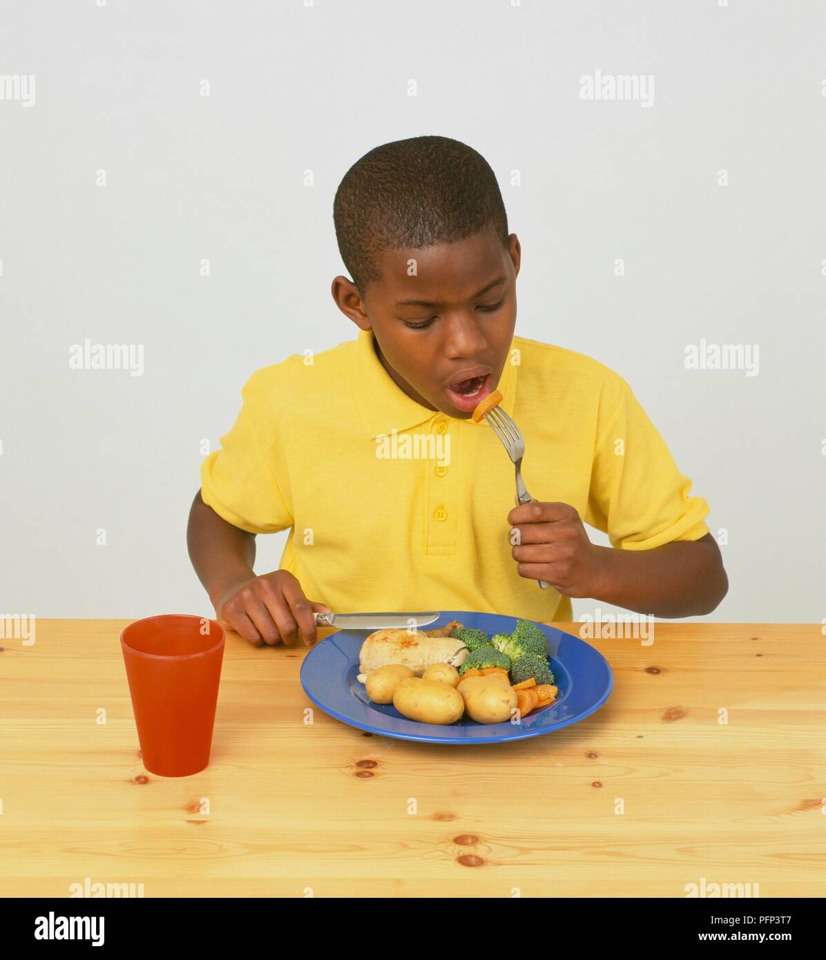Boy in polo shirt sat at table eating from plate of vegetables and meat Stock Photo