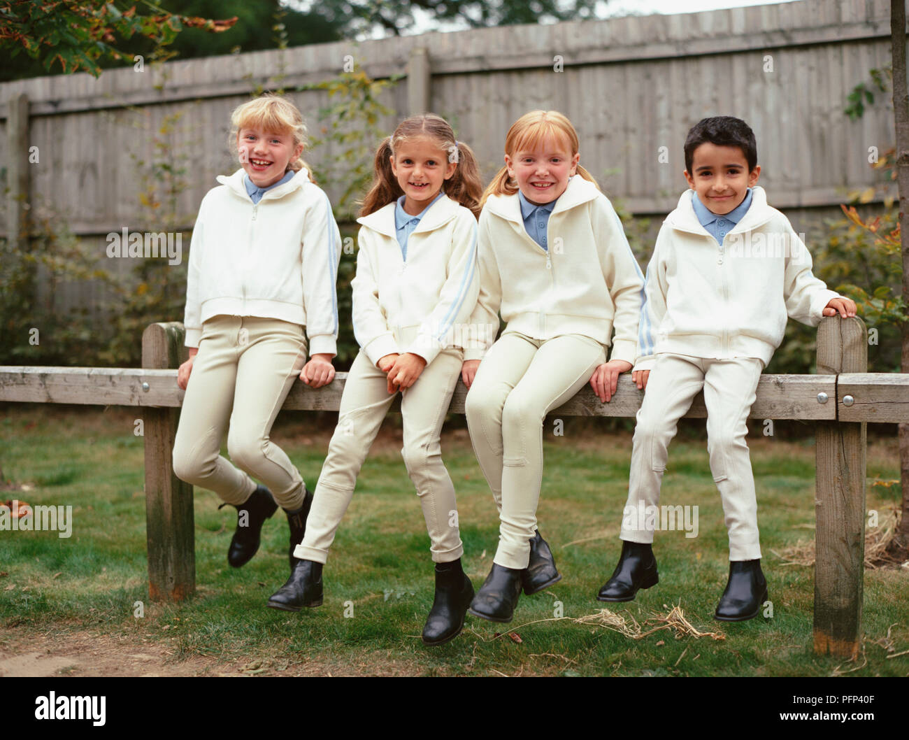 Three Young Girls And A Boy Sitting On A Fence Wearing Horse Riding Clothes Stock Photo Alamy
