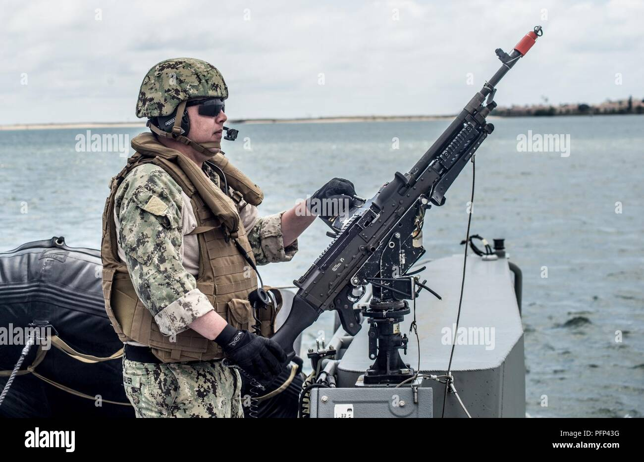 SAN DIEGO (May 23, 2018) Hull Maitenance Technician 2nd Class Tim Salyer assigned to Coastal Riverine Squadron (CRS) 3 mans athe M240 machine gun aboard Mark VI Patrol Boat during high value asset (HVA) escort mission as part of final evaluation problem provided by Coastal Riverine Group (CRG) 1 Training and Evaluation Unit. CRG provides a core capability to defend designated high value assets throughout the green and blue-water environment and providing deployable Adaptive Force Packages (AFP) worldwide in an integrated, joint and combined theater of operations. - Stock Image