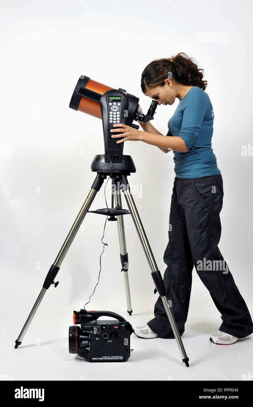 Woman looking through eyepiece on astronomical telescope, side view