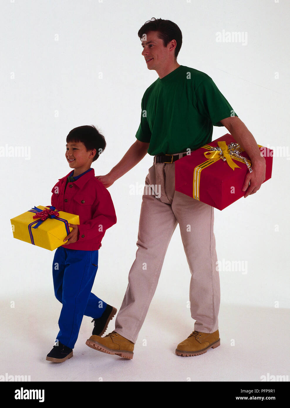 Father and son walking carrying birthday presents - Stock Image