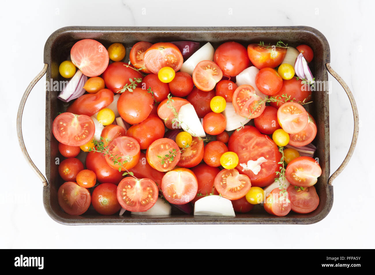 Tomatoes, Onions and Garlic ready for roasting. - Stock Image
