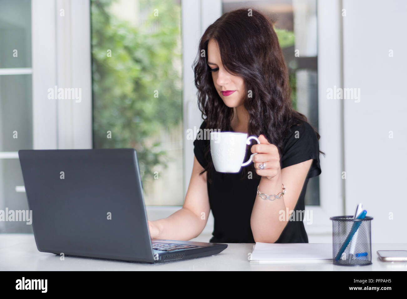 Beautiful young girl working on laptop at office desk and drinking cup of coffee. Modern business and job concept. Close up, selective focus - Stock Image