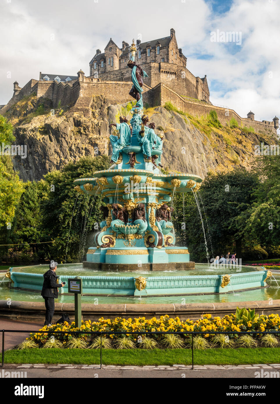 A tourist with a camera admires the refurbished Ross Fountain in West Princes Street Gardens, in front of Edinburgh Castle. Scotland. Stock Photo
