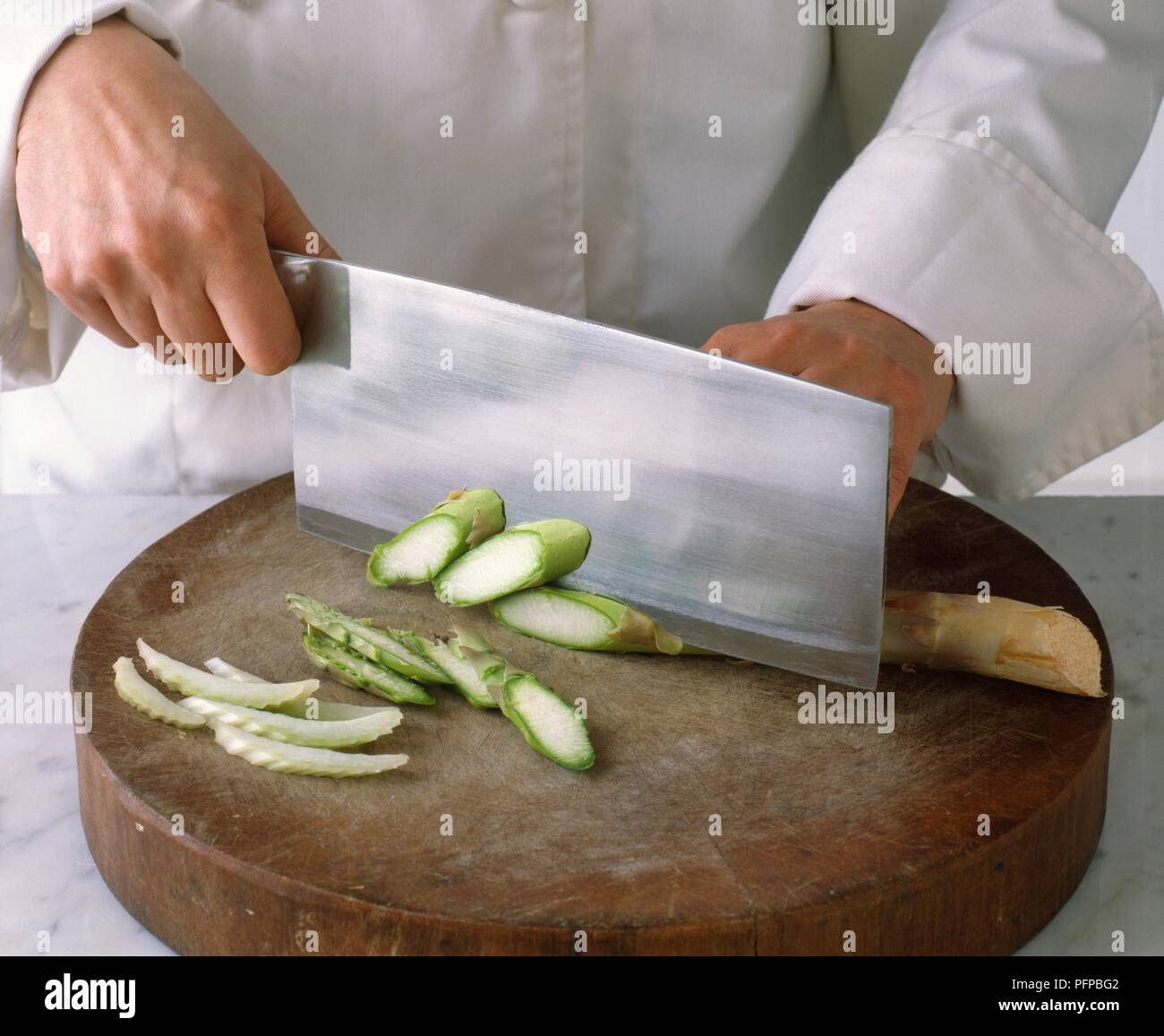 Chef's hands chopping asparagus with cleaver, chopped fennel nearby, close-up Stock Photo
