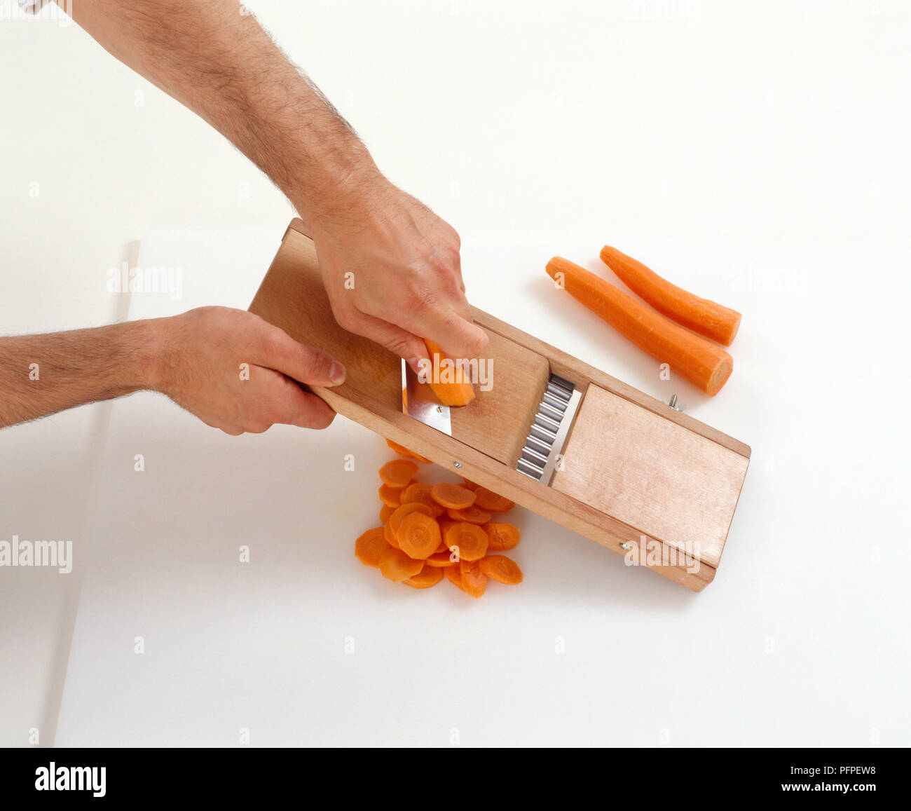 Slicing carrots with a mandolin slicer Stock Photo