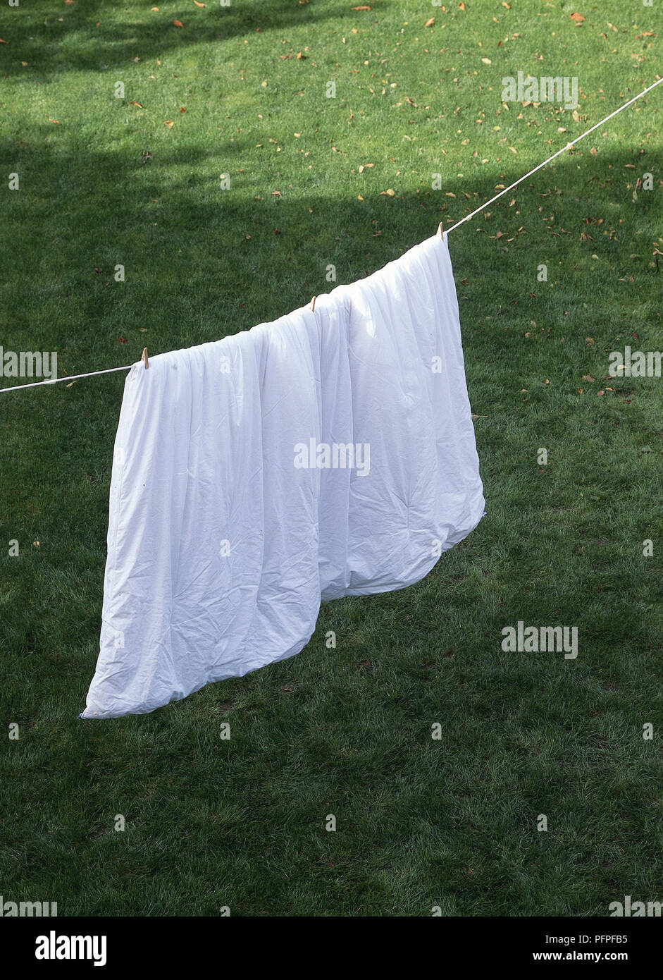 Duvet hanging out to air on washing line above garden lawn. - Stock Image