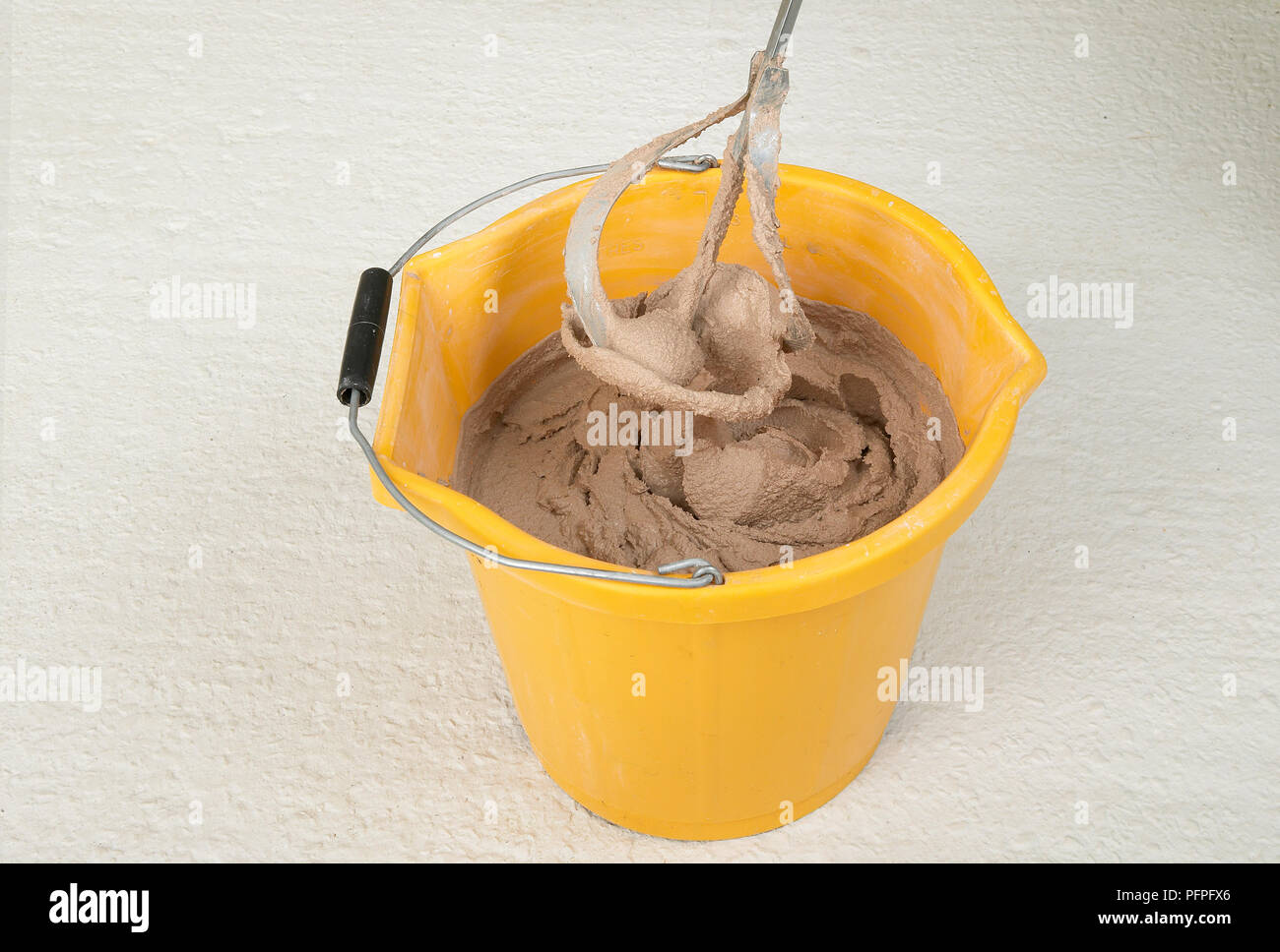 Electric stirrer in bucket of plaster Stock Photo