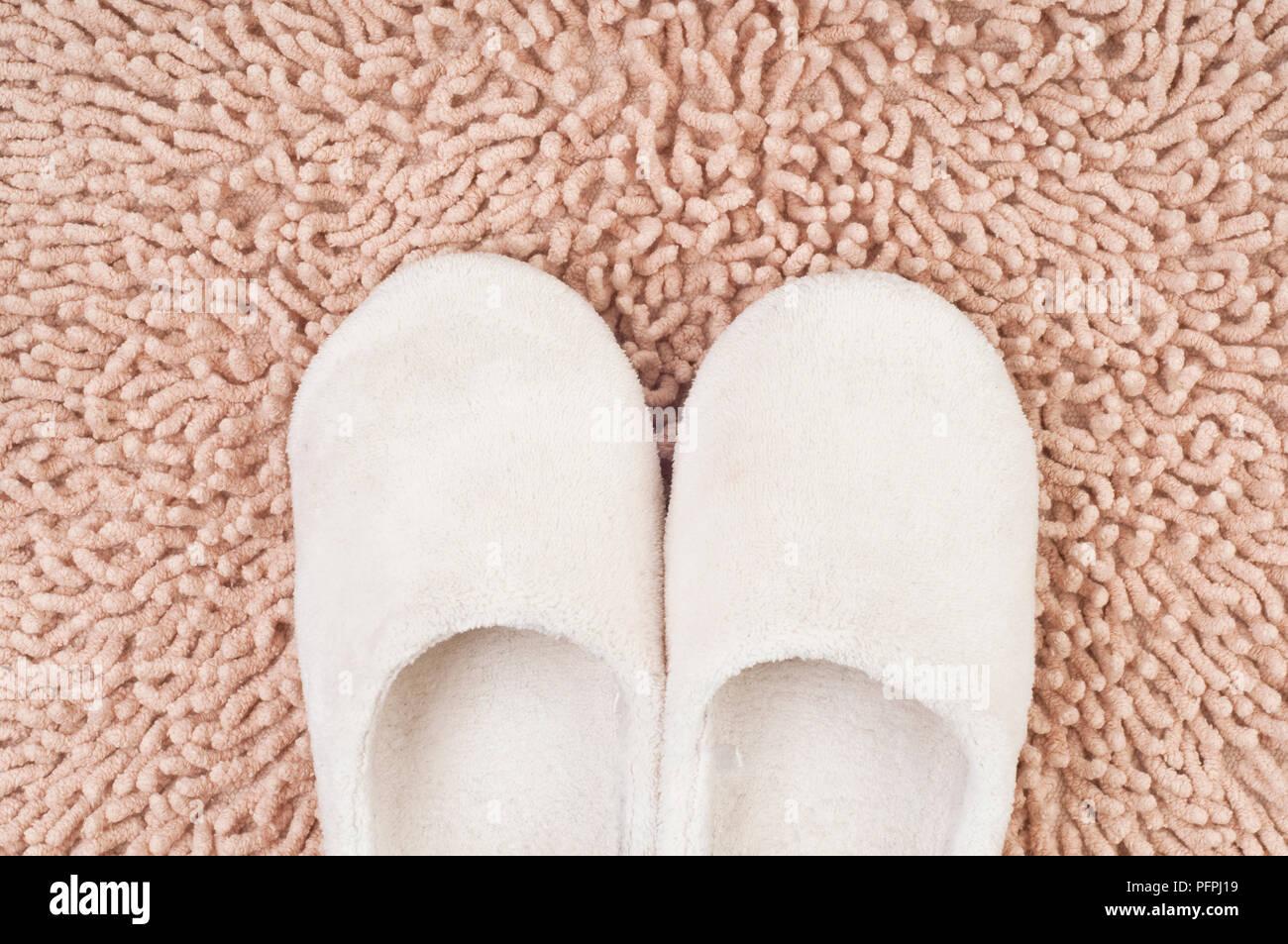 Pair of soft white children's slippers on beige shag pile carpet, overhead view - Stock Image