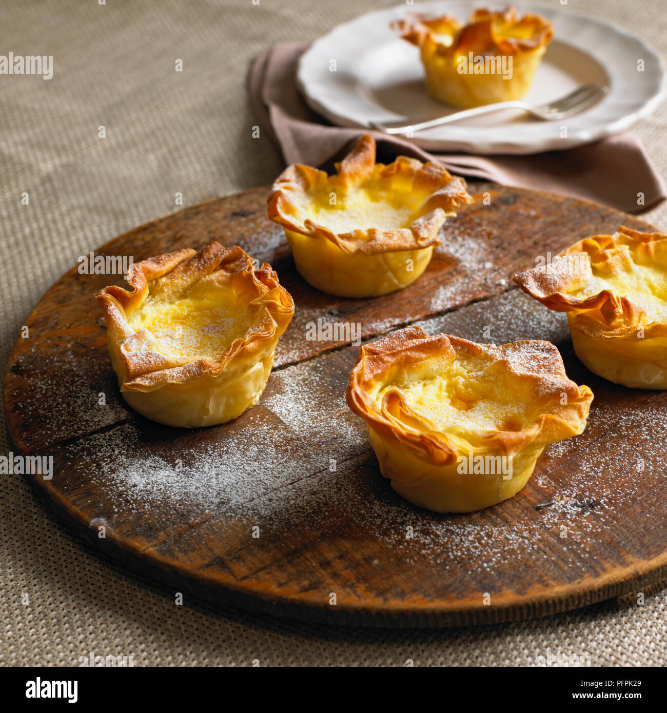 Cardamom custard filo tartlets dusted with icing sugar, on wooden board - Stock Image