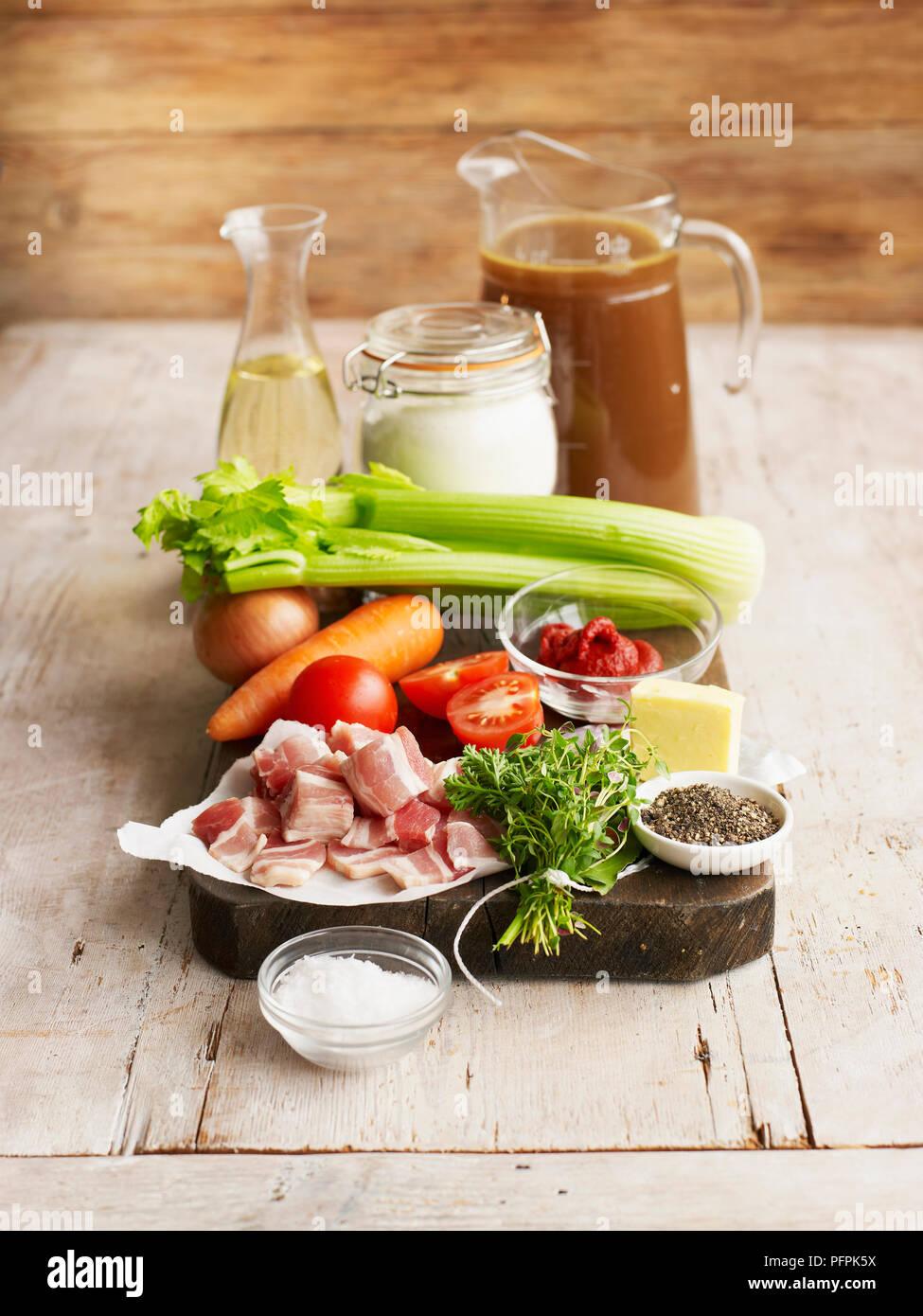 Ingredients for espagnole sauce, including jug of meat stock, vegetables, bouquet garni, pepper and salt, flour - Stock Image
