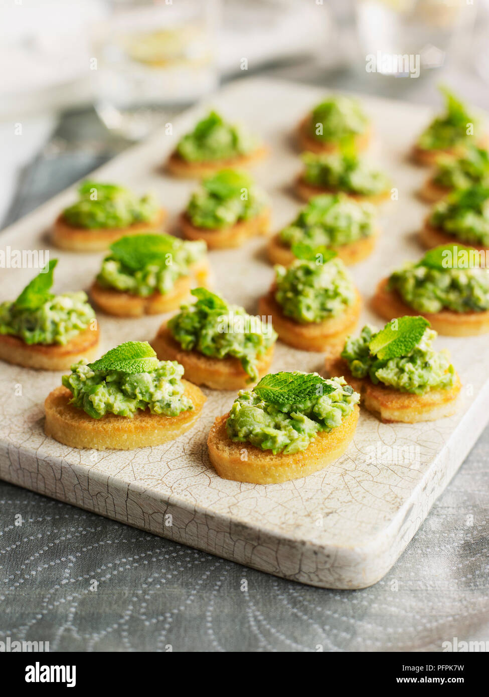 Minted crushed pea and lettuce crostini garnished with mint sprigs - Stock Image