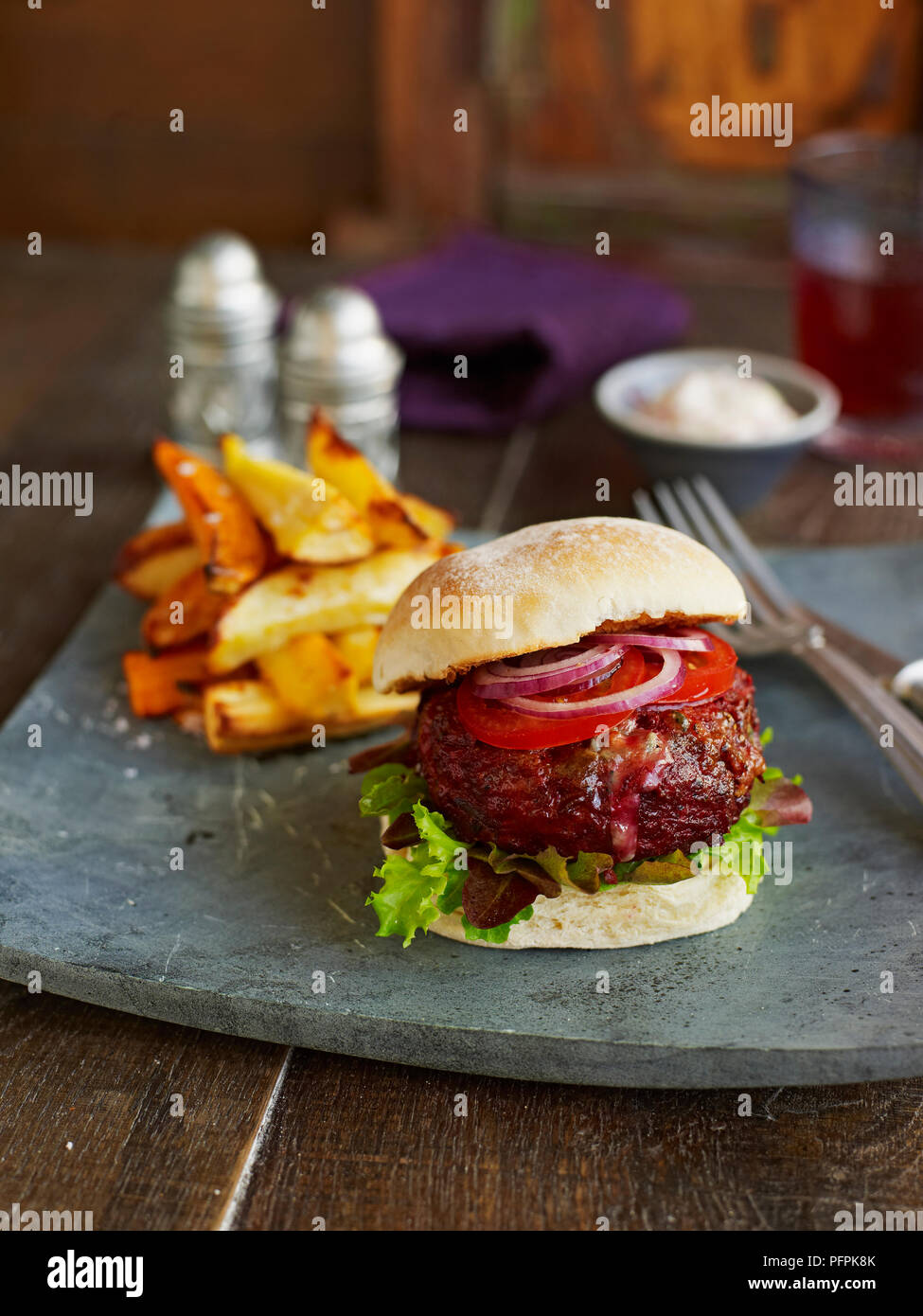 Beef, beetroot and stilton burger in bap, served with veggie chips - Stock Image