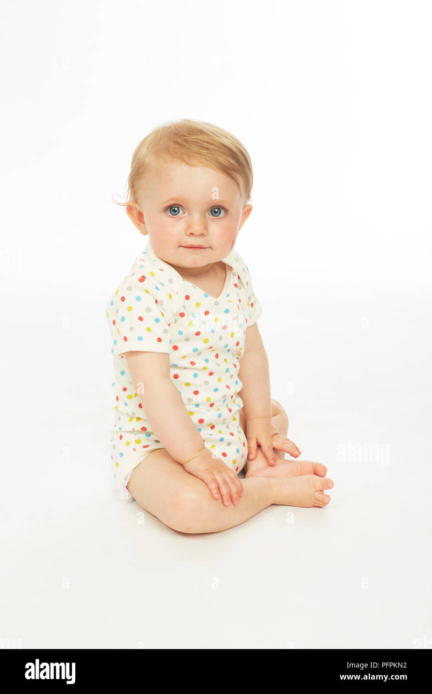 Baby in playsuit sitting  (Model age - 9 months) - Stock Image
