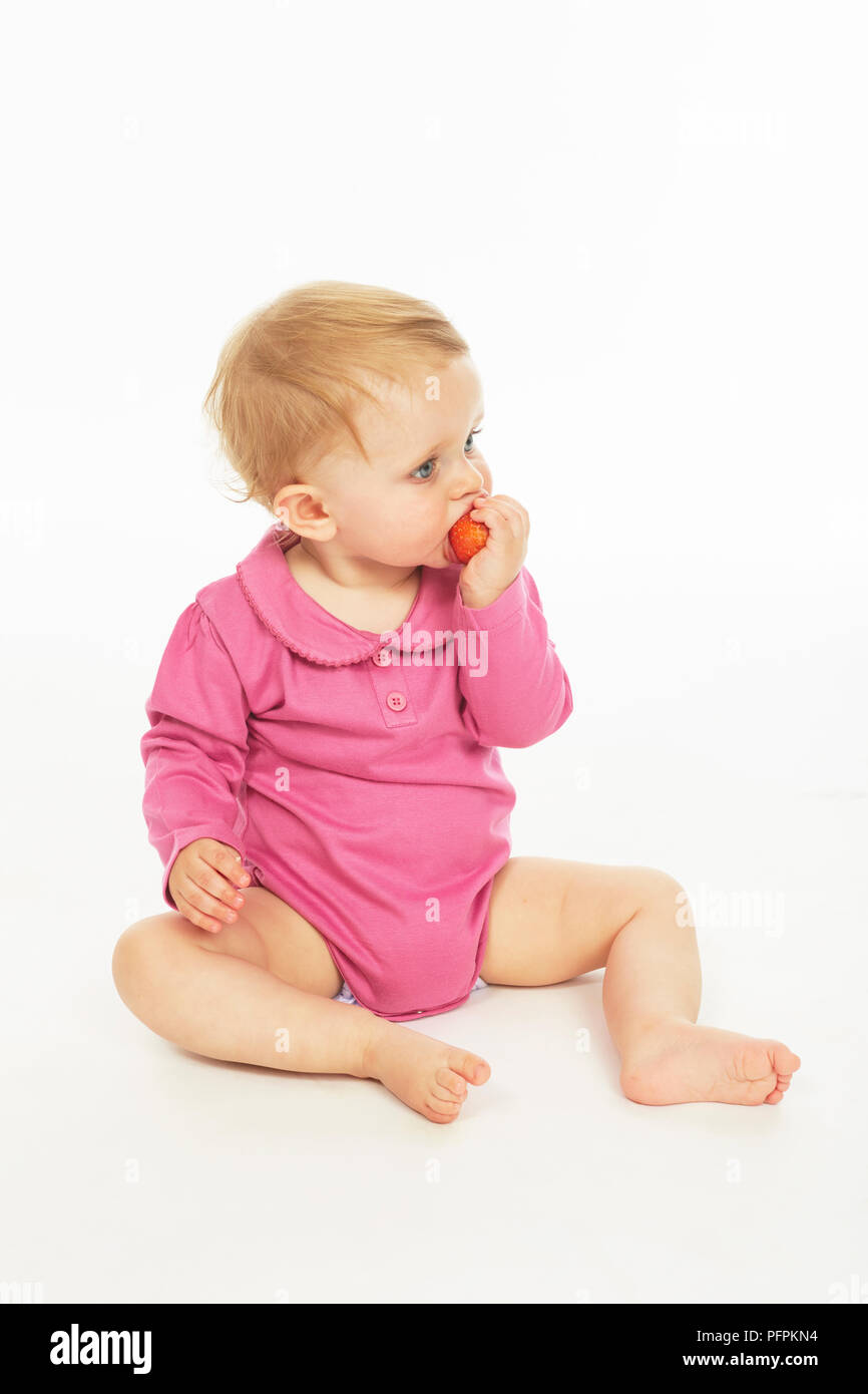 Baby in pink playsuit eating strawberry  (Model age - 9 months) - Stock Image