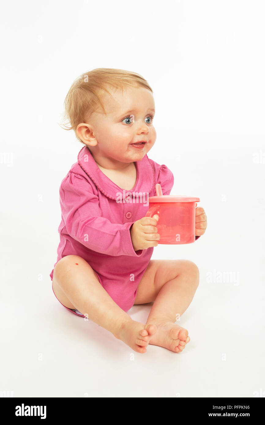 Baby in pink playsuit drinking  (Model age - 9 months) - Stock Image